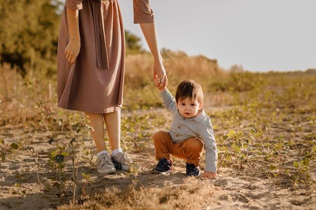 Мама держит за руку своего годовалого малыша на прогулке в парке у реки.
