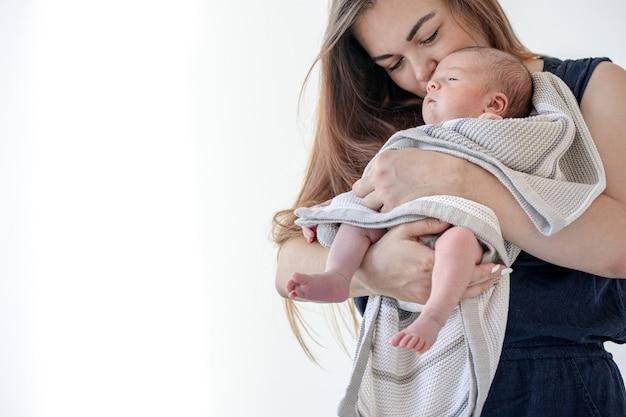 ママは、毛布に包まれた生まれたばかりの女の子を腕に抱き、コピースペースを作ります。