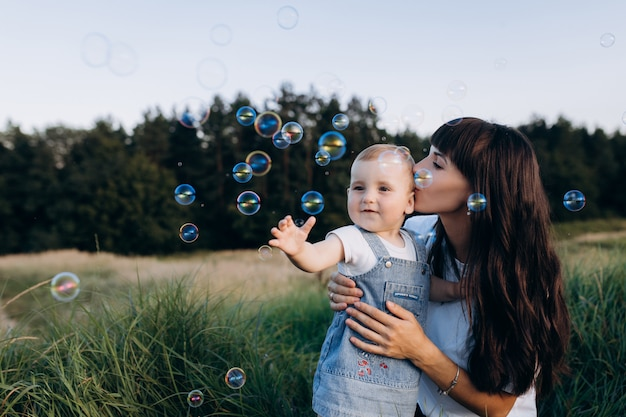 Mom holds little daughter on her arms while soap balloons fly around them
