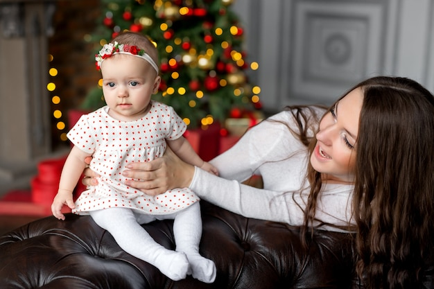 ママは花輪とカラフルなボケ味でクリスマスツリーのそばで陽気に笑っている小さな娘を保持します
