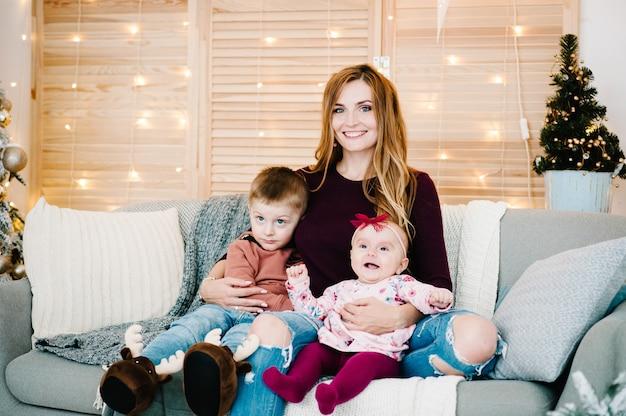 Мама обнимает сына, дочь сидит на диване возле елки с новым годом и рождеством