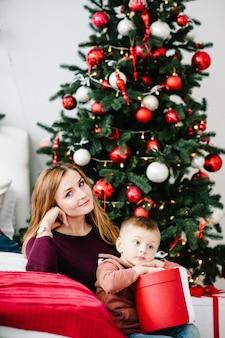 Мама обнимает сына с подарком возле елки с новым годом и рождеством