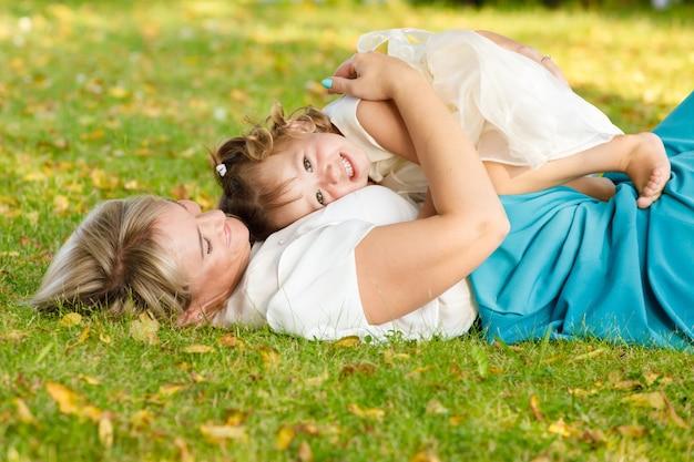 天気の良い夏、お母さんは公園で幼い娘を抱きしめた