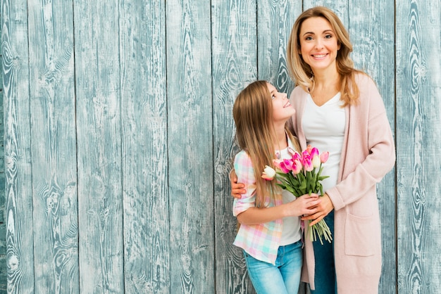 Mom hugging daughter and smiling with flowers