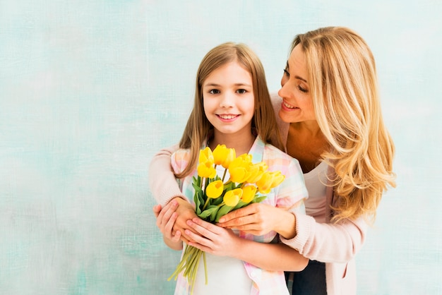 Mom hugging daughter with tulips and looking at girl