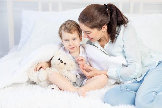 ママはベッドで赤ちゃんを抱きしめる、家族と子供たちの概念、母の日