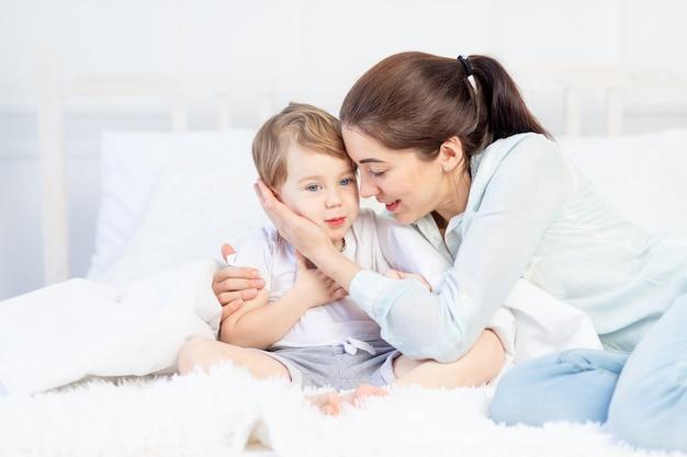 ママはベッドで赤ちゃんを抱きしめる家族と子供の母の日の概念