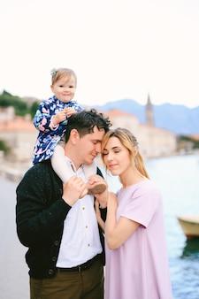 엄마는 바다 산과 오래된 건물을 배경으로 어깨에 딸을 안고 아빠를 껴안습니다
