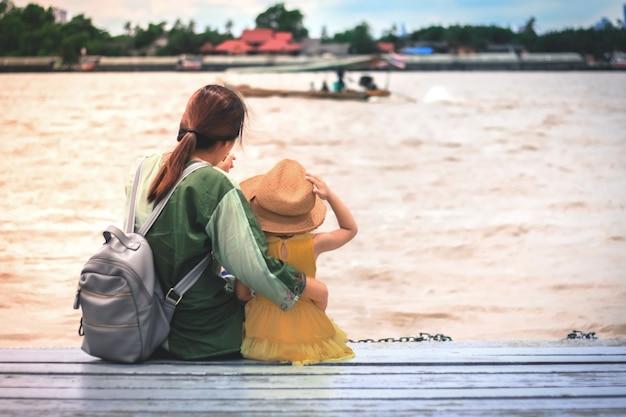 Мама обнимает дочь с видом на озеро