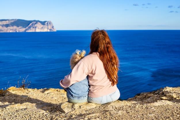 ママは彼女の赤ん坊の娘を抱きしめ、壮大な海の景色のリアビュー旅行の概念を見ます