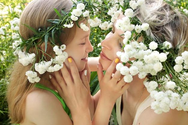 ママは夏の花の設定に対して彼女の娘を抱きしめます