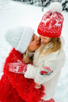 Mom hugs her daughter . family portrait against the backdrop of a snowy yard. family look.