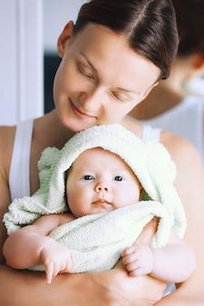 엄마는 목욕 후 머리에 수건으로 가장 귀여운 아기를 안아줍니다. 가족 생활 엄마와 아기