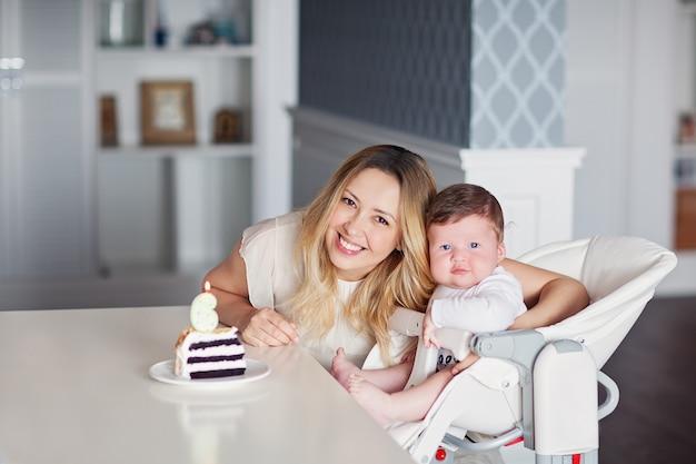 엄마는 테이블 위에 숫자 6이 적힌 케이크 한 조각인 유아용 식사 의자에 아들을 안고 있습니다. 고품질 사진