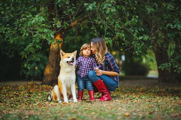 Мама обнимает сына возле красной собаки акита-ину в осеннем парке