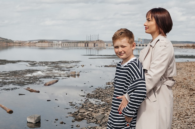 Mom hugs her son on the riverbank. a beautiful, modern mother with a happy son in striped vests.