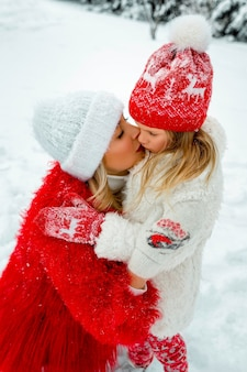 Mom hugs and kisses her daughter on the cheek. family portrait against the backdrop of a snowy yard. family look.
