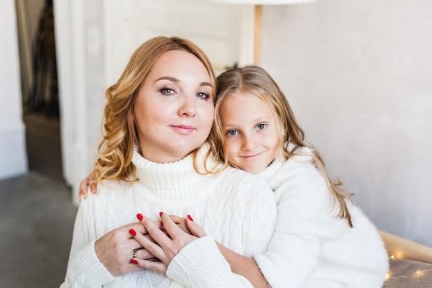Мама обнимает маленькую дочку, сидящую на диване в легких платьях