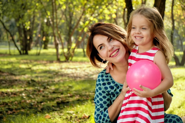 Mom hugs a little girl holding a balloon in the park