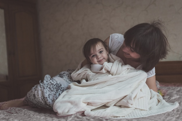 Mom hugs and plays with her daughter hide and seek on  bed, lifestyle,