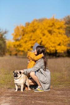Мама обнимает ребенка на осенней прогулке с собакой в парке.