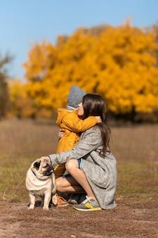 ママは公園で犬と一緒に秋の散歩で子供を抱きしめます。