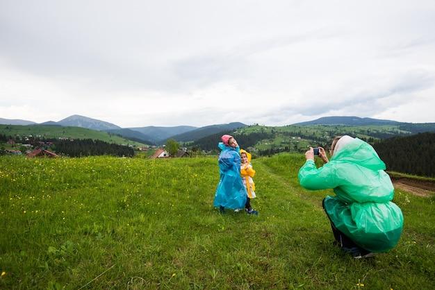 Мама в плаще фотографирует двух своих симпатичных детей в плащах на фоне живописных лугов, холмов и гор в сельской местности. концепция отпуска страны.