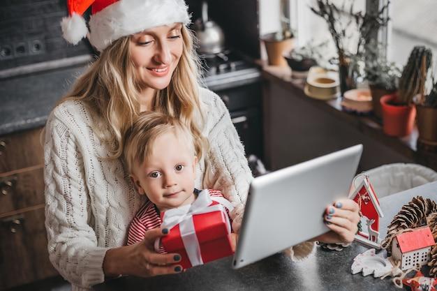 Мама в шапке санты сидит с ребенком дома, держит планшет и делает видеоконференцсвязь.