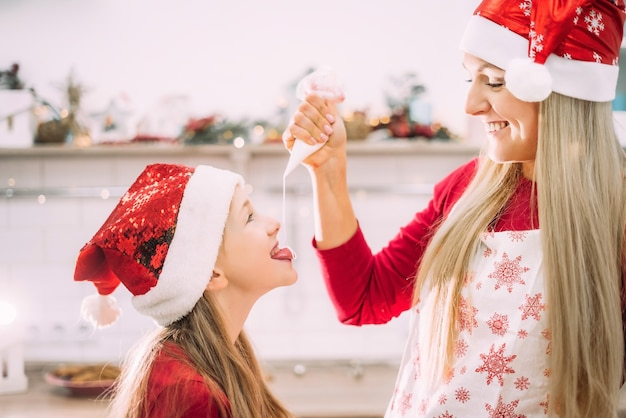 Мама в фартуке и ее дочь-подросток веселятся на кухне в шляпах санты.