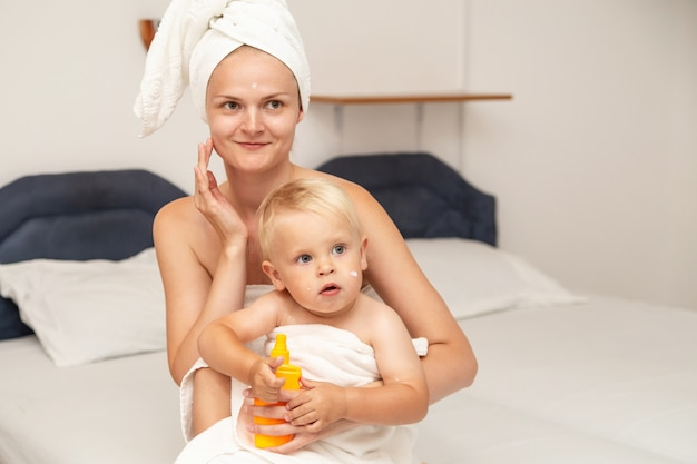 Mom and infant baby in white towels after bathing apply sunscreen or after sun lotion or cream