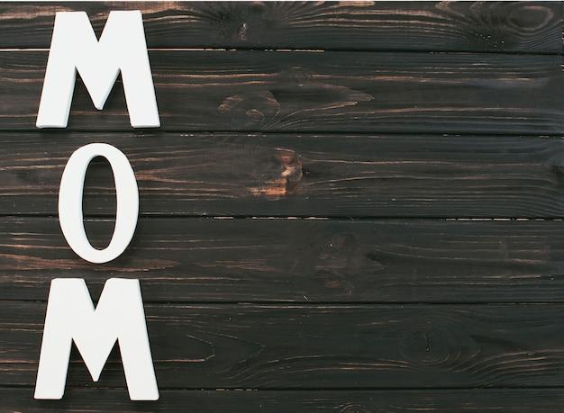 Mom inscription on dark wooden table