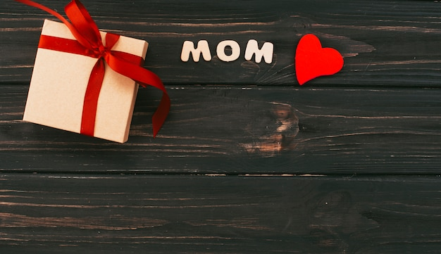 Mom inscription with gift box on wooden table