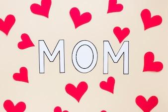 Мама надпись с бумажными сердечками на столе