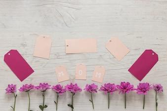 小さな紫色の花を持つお母さん碑文