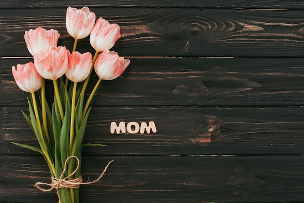 Mom inscription with tulips bouquet on table