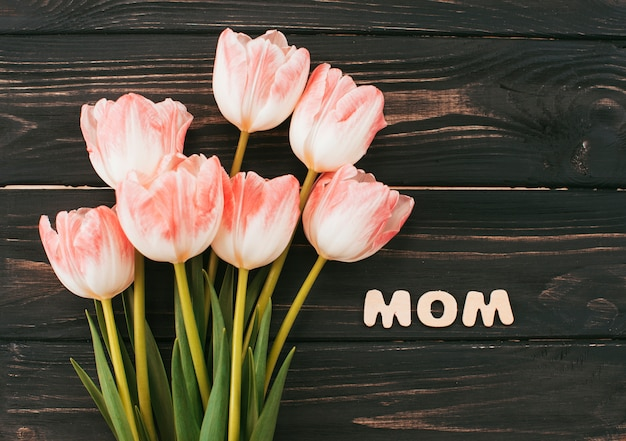 Mom inscription with tulips bouquet on wooden table