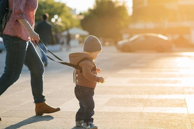 Мама страхует своего ребенка во время прогулки