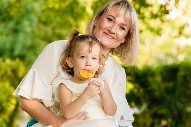 ママは甘いロリポップを持っている彼女の腕の中に娘を持つブロンドです。夏の公園で