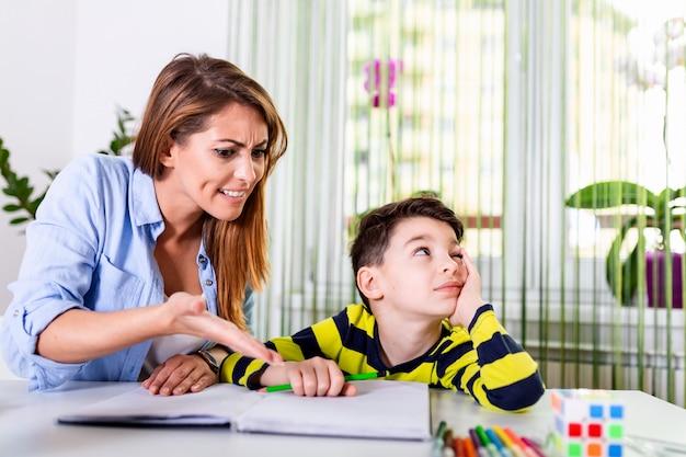 엄마는 아들이 숙제를하고 싶지 않기 때문에 화가납니다. 어머니와 아들은 실패 숙제에 좌절했다.