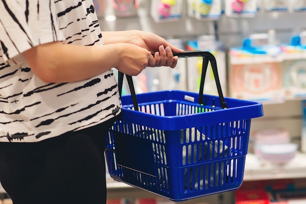 ママはスーパーマーケットで生まれたばかりのベビー用品を選んでいます。妊娠と買い物。
