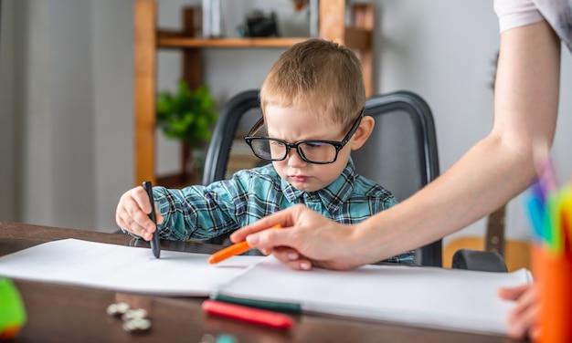엄마는 귀여운 아이가 테이블에있는 앨범의 종이에 연필로 그림을 그릴 수 있도록 돕고 있습니다.