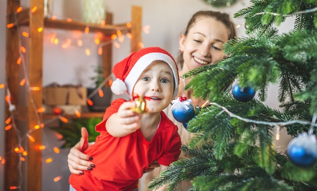 Mom is helping her child son decorate the christmas tree