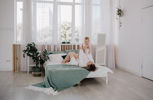 ママはベッドに横になっていて、部屋で娘の赤ちゃんを迎えに行きます
