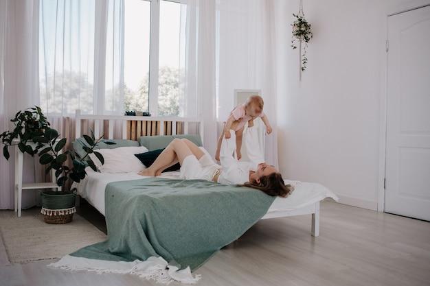 Мама лежит на кровати и играет со своей маленькой дочкой в розовом боди.