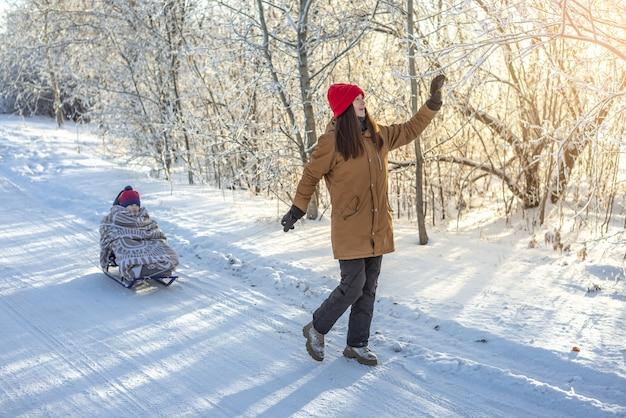 凍るような冬の晴れた日を戸外で歩いているそりでお母さんが子供を引っ張っている