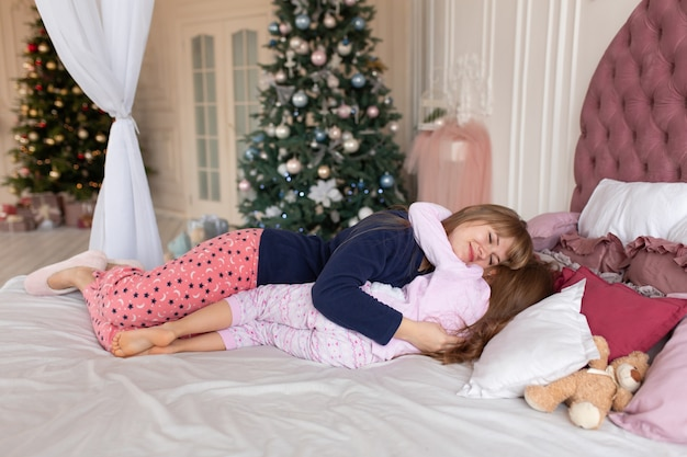 Mom is putting the little girl to bed on christmas night. christmas tale. happy childhood.