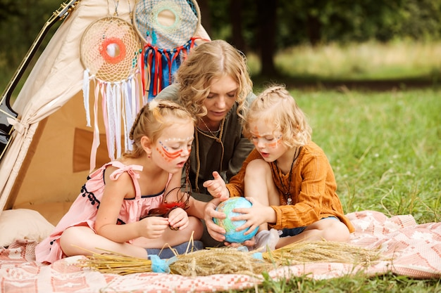 Mom is spending time with her little daughters, teaching them geography in a playful way.