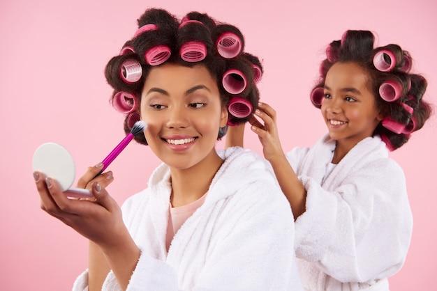 소녀가 머리를 땋는 동안 엄마는 아름다움을 입고 있습니다.
