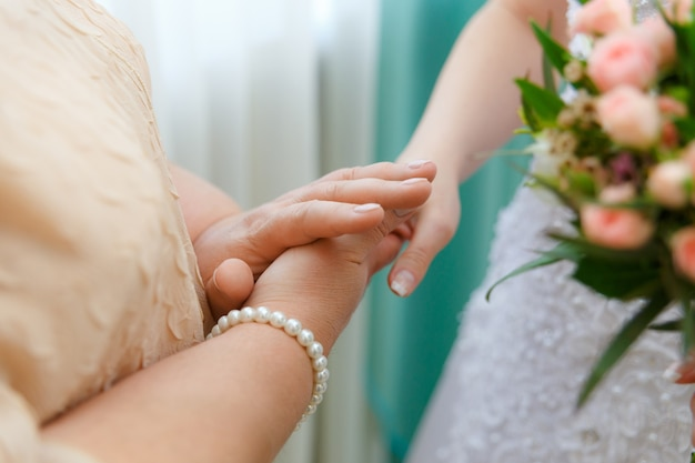 Mom keeps her daughter by the hand on the wedding day. emotional concept.