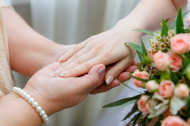 Mom keeps her daughter by the hand on the wedding day.